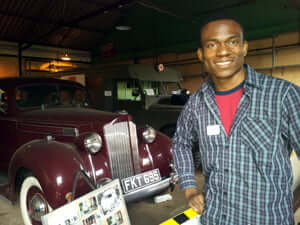 Chukwuemeka Eze with some of the vintage cars at Bletchley Park