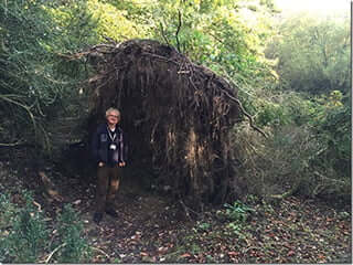 """David Jacques next to the Stone Age """"eco"""" home"""