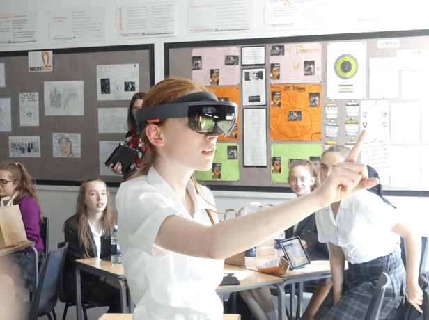 A school age girl wearing an augmented reality headset