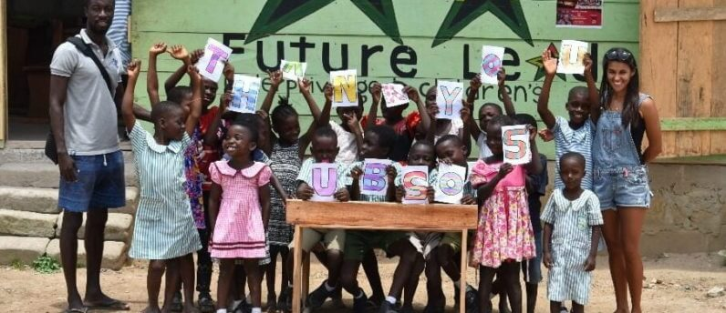 school children that university of buckingham supporting overseas schooling helped raise money for holding up a sign saying thank you