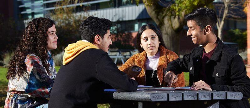 Group of students sat at a picnic bench