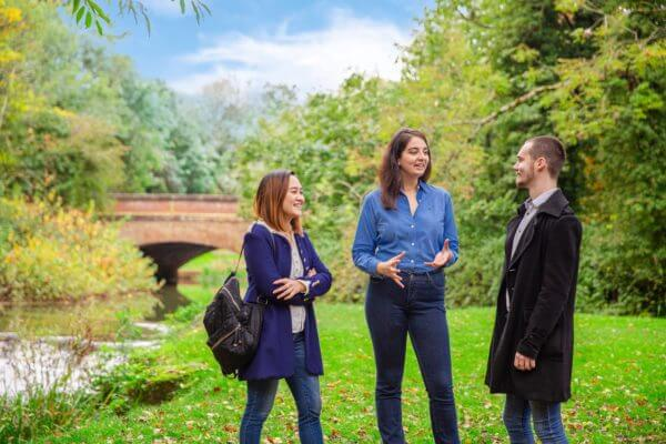 Three people stood by the river on the University of Buckingham campus